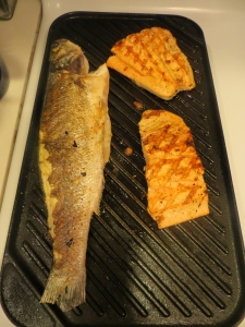 Branzino and salmon on cast iron skillet